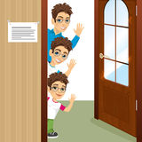 Three brothers with glasses peeking of the door waving. Portrait of three brothers with glasses peeking of the door waving Royalty Free Stock Image
