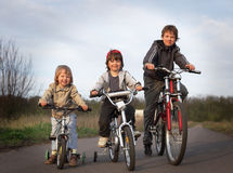 Three brothers ride bikes Royalty Free Stock Photo