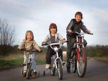 Three brothers ride bikes Royalty Free Stock Photo