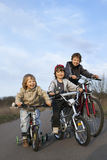 Three brothers ride bikes Stock Images