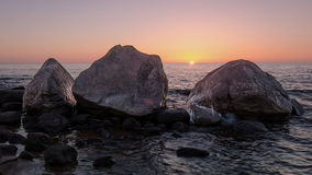 Three brothers rock on the beach at sunset hour. Royalty Free Stock Image