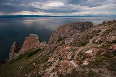 Three Brothers Rocks on Olkhon Island on Lake Baikal on a cloudy day. In the water, a beautiful reflection of the sky. stock image