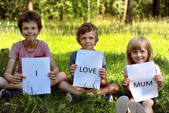 Three brothers with sign I love mum Royalty Free Stock Photos