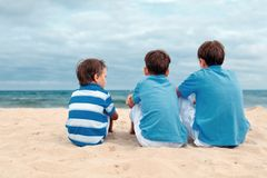 Three brothers are sitting on beach Royalty Free Stock Photography