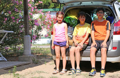Three brothers sitting in the trunk of the car during the summer Royalty Free Stock Photos