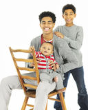 Three Brothers Together. A portrait of three widely-spaced brothers -- the oldest sitting on a chair backwards while holding his baby brother, his elementary royalty free stock photography
