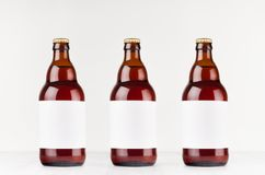 Three brown belgian steinie beer bottles 500ml with blank white label on white wooden board, mock up. stock photography