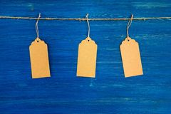 Three brown blank paper price tags or labels set hanging on a rope on the blue background. Royalty Free Stock Photos