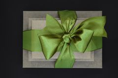Three brown carton gift boxes bundled with green ribbon isolated on black background and view from above royalty free stock photos