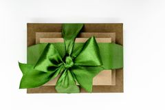 Three brown carton gift boxes bundled with green ribbon isolated on white background and view from above.  royalty free stock photography