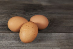 Three Brown Chicken Eggs. One with freckles, on rustic wooden surface stock photography