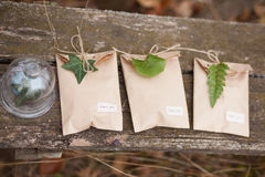 Three brown craft gift boxes. Decorated with fern and ivy leaves with glass box on wooden background Royalty Free Stock Images