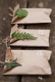 Three brown craft gift boxes. Decorated with fern and ivy leaves on wooden background Stock Photos