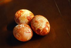 Three brown Easter hand-painted eggs on the brown table Stock Photo