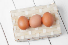 Three brown eggs on basket on a wooden background. Stock Photography