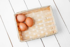 Three brown eggs in basket on a wooden background. Stock Photos