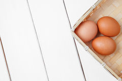 Three brown eggs in basket on a wooden table. top view. horizontal shoot Stock Photos