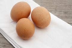 Three Brown Eggs on a Wooden Background Stock Photo