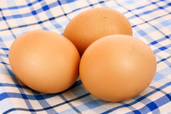 Three brown hen's eggs on the blue Stock Images