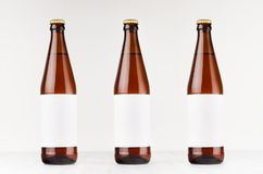 Three brown NRW beer bottles 500ml with blank white label on white wooden board, mock up. Stock Photos