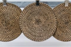 Three brown wicker woven patterns hanging against white wall stock images