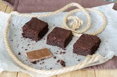 Three brownie pieces and broken chocolate on baking paper Royalty Free Stock Image