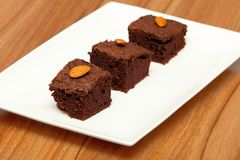 Three brownies with almonds on a white plate Royalty Free Stock Photos