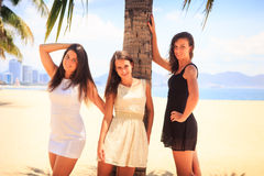 Three brunette slim girls barefoot stand on beach Royalty Free Stock Photos