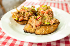 Three bruschettas with tuna lying on plate at restaurant Royalty Free Stock Photo