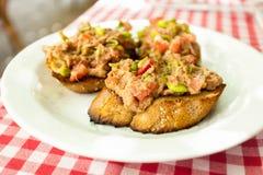 Three bruschettas with tuna lying on plate at restaurant Royalty Free Stock Photo