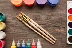 Top view of three brushes, gouache, watercolor and acrylic paints on wooden table. royalty free stock photo