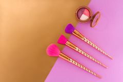 Three brushes and eyeshadow on a double purple - copper-gold background. stock photography