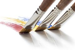 Three brushes painting colors. On white background Stock Images