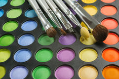 Three Brushes on the palette of eye shadows Stock Image