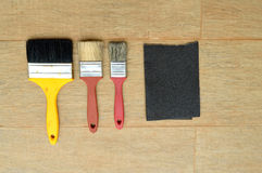 Three brushes and a sandpaper. In a wood background Royalty Free Stock Photography