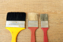 Three brushes. In a wood background Stock Images