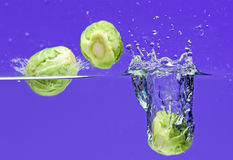 Three Brussels sprouts falling in water Royalty Free Stock Photos