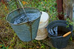 Three buckets of water are on the street in the green grass stock photos