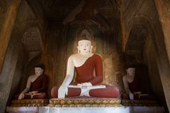 Three Buddha Statues Inside A Temple In Bagan Stock Photos