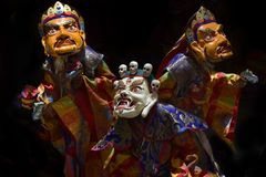 Three Buddhist manahs in ancient ritual robes perform the performance of Lama's Dance in Masks, the White Mask of Mahakala and th. Three Buddhist manahs in Stock Image