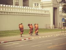 Three Buddhist monks in front of royal palace Bangkok. Three Buddhist monks in orange robe in front of the royal palace in bangkok. They walking the streets Royalty Free Stock Photo