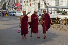Three Buddhist monks walking down a street in Yangon, Myanmar stock images