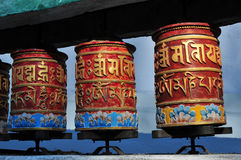 Three Buddhist prayer drums of red color with yellow hieroglyphs mantra against a blue sky background on a clear day. Three Buddhist prayer drums of red color Royalty Free Stock Photo