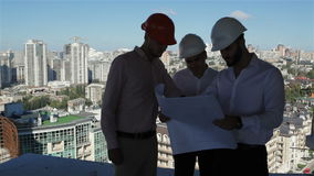 Three builders examine the project of building under construction. Three male builders examining the project of bulding under construction. Three construction stock footage