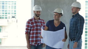 Three builders pose at the building under construction stock video