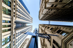 Three buildings overhead and the sky. Extreme perspective looking straight up from the center of a street intersection with three buildings from each corner Stock Photos