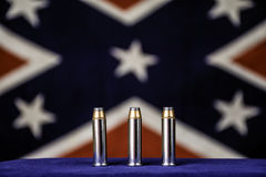 Three Bullets. Three 357 magnum bullets on blue in front of confederate flag royalty free stock photography