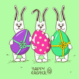 Three bunny rabbits holding Easter eggs Stock Photos
