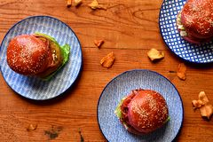 Three burgers on blue plates royalty free stock photos