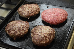 Three burgers cocked and one starting to cook. Cooking hamburgers steaks in a grill on a gas cooker Royalty Free Stock Images